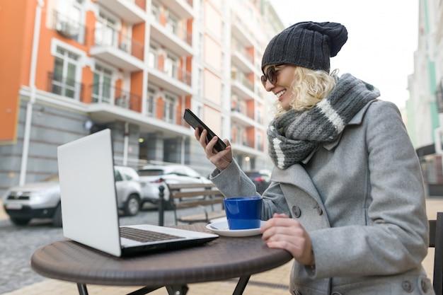 Blogueur enseignant jeune femme avec des lunettes dans un café en plein air