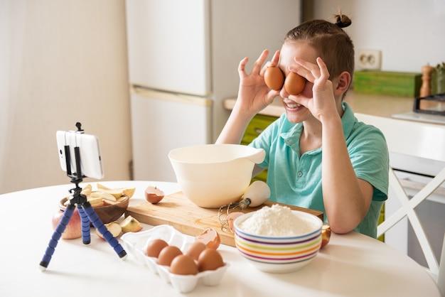 Un blogueur gastronomique cuisine dans la cuisine lors d'une épidémie de coronavirus. met des œufs dans vos yeux
