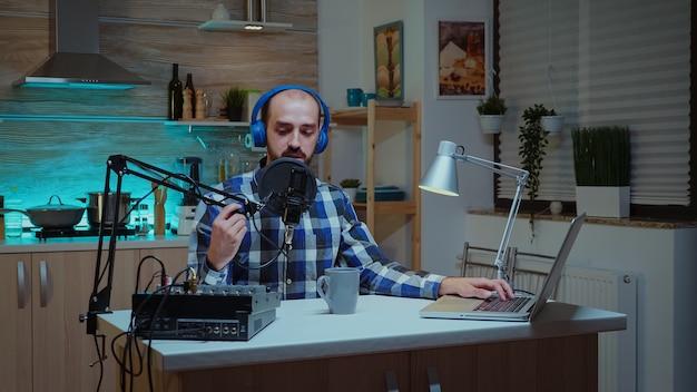 Un blogueur homme portant des écouteurs et parlant de son mode de vie pendant un podcast depuis son domicile. spectacle en ligne créatif production en direct hôte de diffusion sur internet diffusant du contenu en direct, enregistrement de réseaux sociaux numériques