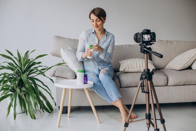 Blogueur de jeune femme enregistrant la vidéo sur l'appareil-photo
