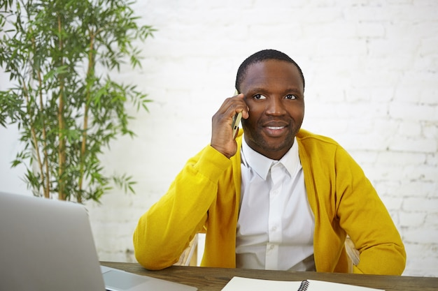Blogueur masculin à la peau sombre à la mode ayant une conversation téléphonique, assis devant un ordinateur portable ouvert, travaillant sur le contenu de son blog de voyage. personnes, travail, profession et gadgets électroniques modernes