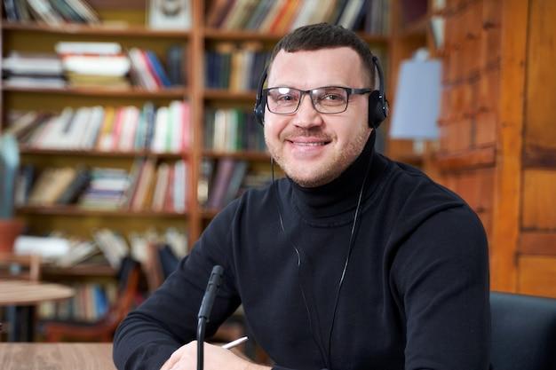 Blogueur masculin en streaming à partir de la bibliothèque à l'aide d'un ordinateur portable et d'un microphone