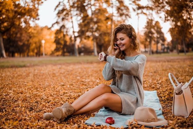 Blogueur de mode attrayante parler au téléphone en automne parc.