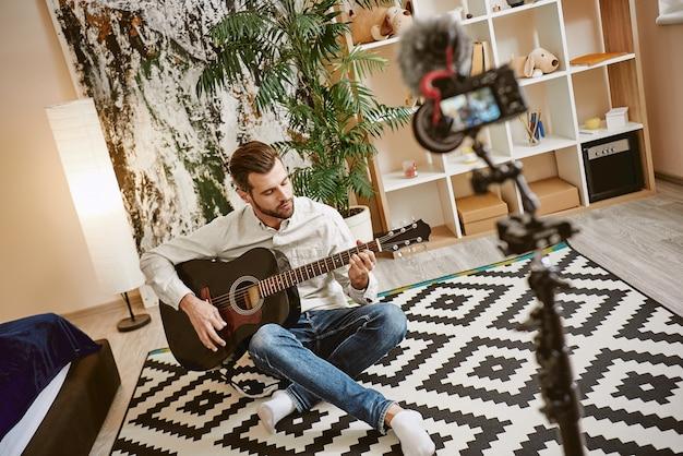 Blogueur de musique séduisant homme barbu assis sur le sol à la maison et jouant sur acoustique