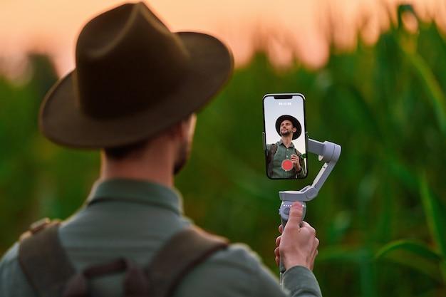 Un blogueur routard voyageur portant un chapeau de feutre avec un cardan stabilisateur de téléphone manuel électronique prend un selfie et filme un blog vidéo à l'extérieur