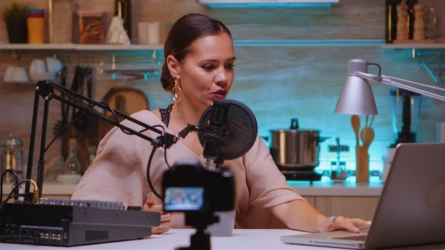 Blogueur saluant la caméra pendant l'enregistrement d'une vidéo et parlant au microphone. spectacle en ligne créatif production à l'antenne hôte de diffusion sur internet en streaming de contenu en direct, enregistrement de la communication numérique sur les médias sociaux