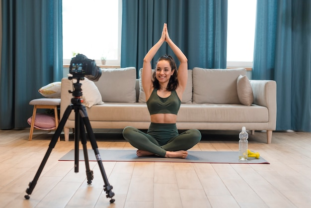 Blogueur sportif assis en position du lotus avec les bras levés
