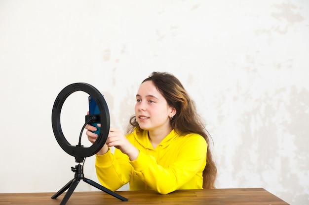 Une blogueuse de 15 ans dirige une émission en direct et s'illumine avec une lampe annulaire dans une pièce lumineuse