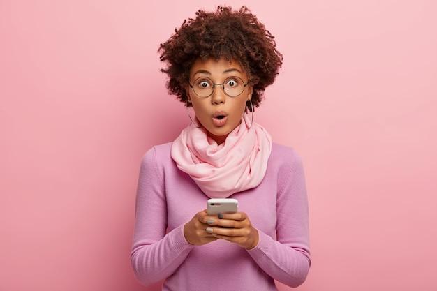 Une blogueuse afro à la peau sombre et surprise émotive fait de la publicité sur un téléphone mobile