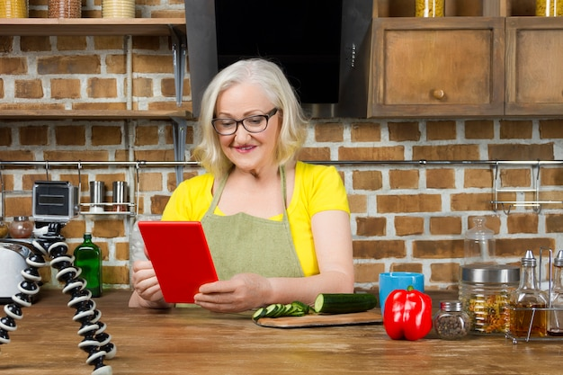 Une blogueuse alimentaire âgée enregistre sa cuisine par caméra vidéo