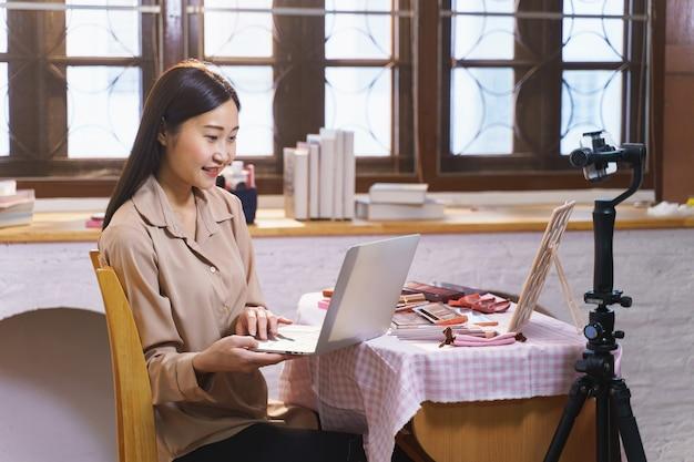 Une blogueuse asiatique sur la beauté a diffusé en direct pour examiner le produit de maquillage sur les réseaux sociaux, une jeune influenceuse moderne démontrant son cosmétique quotidien tout en parlant sur l'appareil photo d'un smartphone
