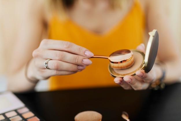 Blogueuse de beauté appliquant une houppette ovale à la poudre de contour