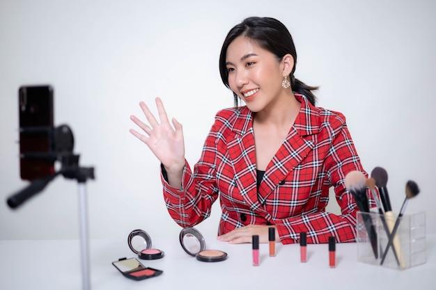 Une blogueuse de beauté asiatique se maquille et évalue un produit de beauté pour un blog vidéo