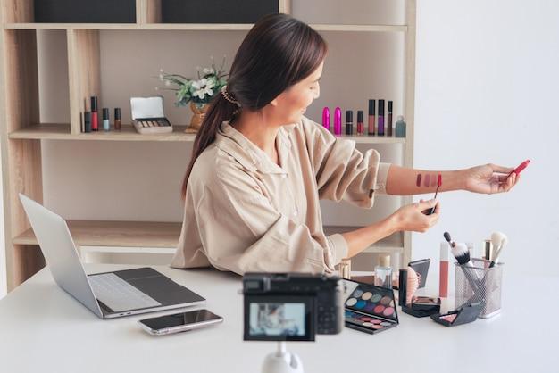 Blogueuse beauté enregistrant une vidéo et présentant des cosmétiques à la maison