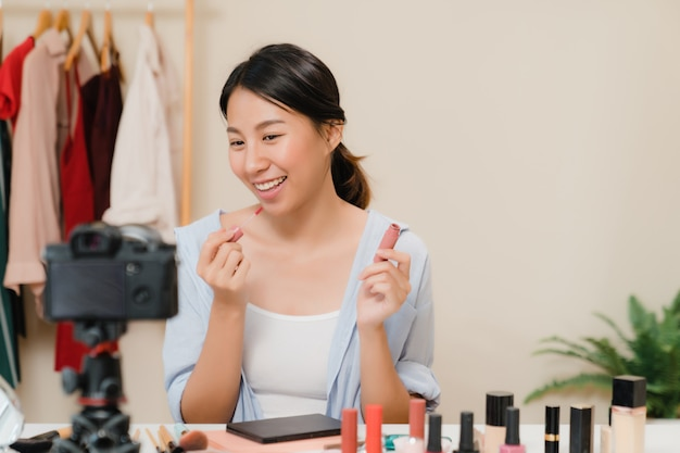 Une blogueuse beauté présente des produits cosmétiques assis devant la caméra pour enregistrer une vidéo.