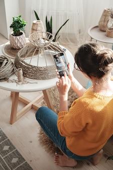 Une blogueuse de bricolage prend une photo sur un téléphone portable pour un blog de bricolage dans une lampe en corde de jute faite à la main dans les médias sociaux