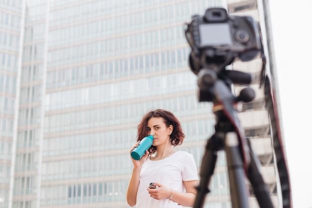 Une blogueuse brune buvant de l'eau à la bouteille