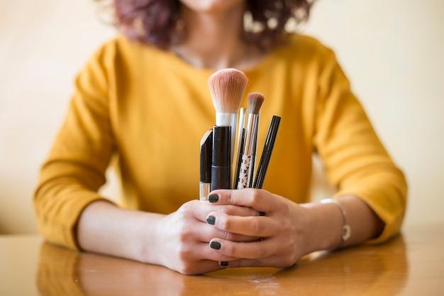 Une blogueuse brune montrant des pinceaux à maquillage