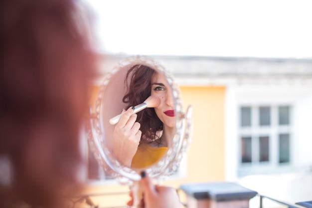Une blogueuse brune se maquillant