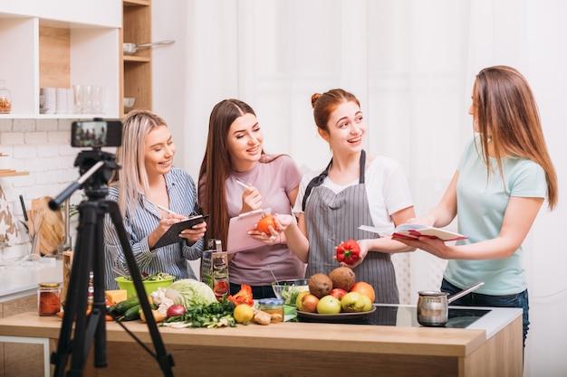 Une blogueuse culinaire enseigne aux femmes une alimentation saine lors de cours culinaires. tutoriel vidéo en ligne de prise de vue.