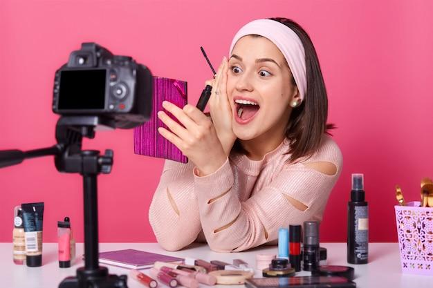 Blogueuse femme ou beauté avec pinceau à paupières, miroir et appareil photo, assis à table, entouré de cosmétiques, enregistrement de maquillage