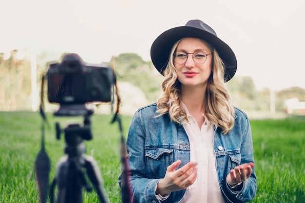 Blogueuse fille élégante assise dans le parc et tire vlog sur caméra.