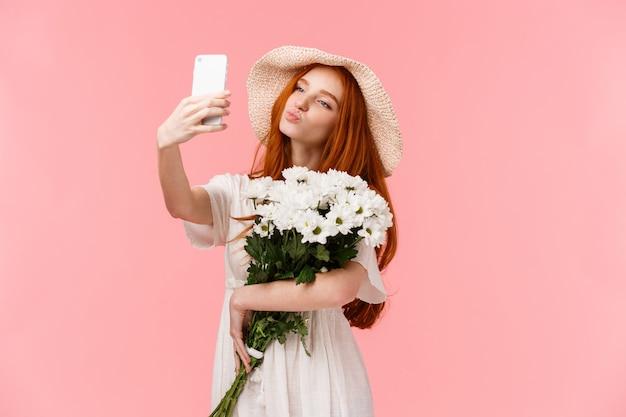 Blogueuse fille idiote et mignonne, féminine, prenant un selfie avec le bouquet de fleurs que son petit ami a apporté, tenant les lèvres pliantes du smartphone dans un baiser aérien, posant pour une prise de vue sensuelle parfaite, tenez-vous rose