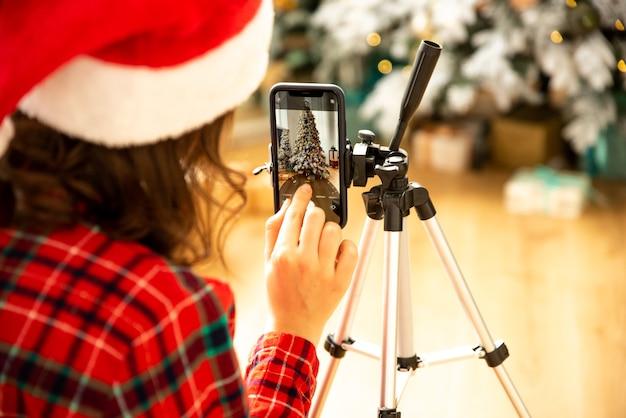 Une blogueuse filme une vidéo ou une photo sur son téléphone sur fond d'arbre de noël. elle a mis un chapeau de père noël.