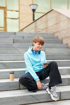 La blogueuse de la jeune femme est assise dans les escaliers avec un smartphone, elle sourit et regarde la caméra à la verticale ...