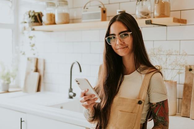 Blogueuse lifestyle utilisant son téléphone portable dans la cuisine