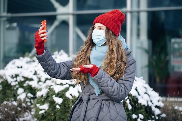 Une blogueuse en masque facial fait une vidéo parlant pour sa page sociale dans la rue en hiver.