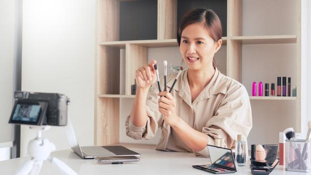 Blogueuse mode enregistrement vidéo présentant des cosmétiques à la maison