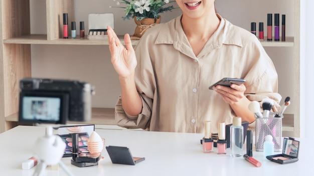 Blogueuse mode enregistrement vidéo présentant des cosmétiques de maquillage à la maison