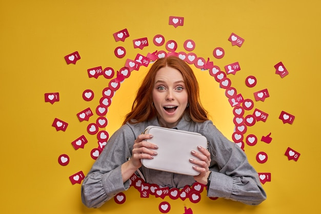 Blogueuse optimiste souriante montrant un nouveau sac à main, attendant la réaction des gens sur internet.