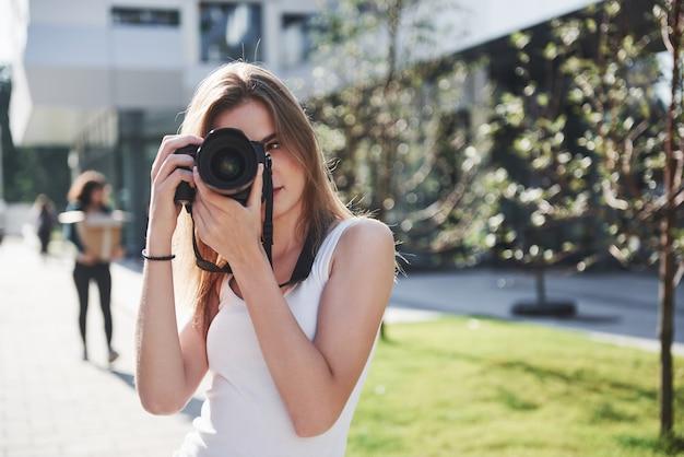 La blogueuse photographe fille tient en main un appareil photo professionnel en plein air dans la ville.