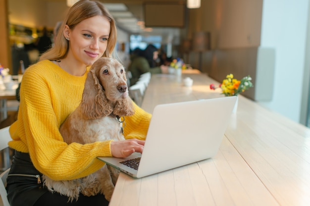 Blogueuse pigiste blonde en sweat jaune à l'aide d'un ordinateur portable dans l'espace de travail co et tenant son vieux chien cocker sur ses genoux