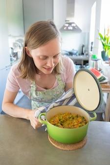 Blogueuse positive cuisinant dans sa cuisine, ouvrant et vérifiant une casserole avec un repas de légumes. tir vertical. concept de blogueur alimentaire