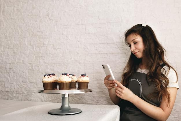 Une blogueuse prend des photos de gâteaux et de cupcakes pour ses abonnés sur son téléphone