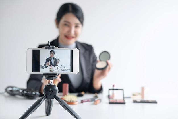 Une blogueuse présente un produit cosmétique beauté et diffuse une vidéo en direct