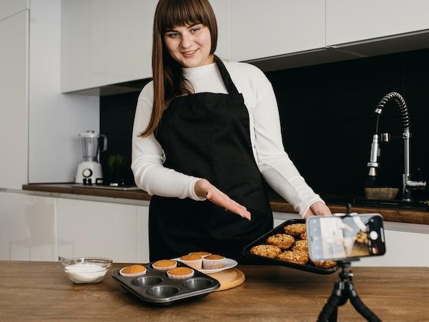 Une blogueuse smiley s'enregistre en préparant des muffins