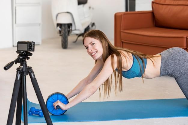Blogueuse sportive se recodant à l'aide d'une roue ab