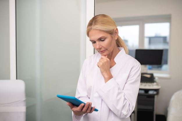 Blond agréable médecin tenant la tablette dans sa main tout en lisant les actualités en ligne