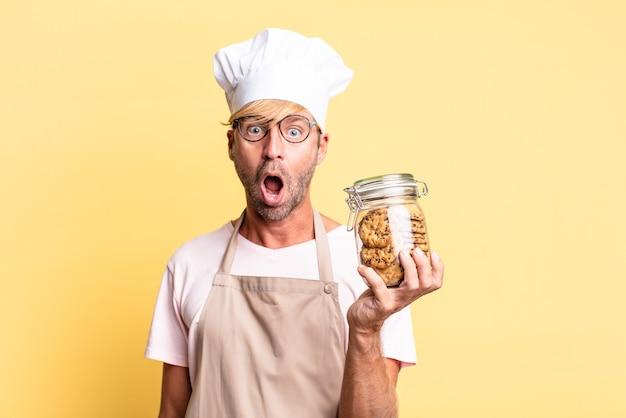 Blond beau chef homme adulte tenant une bouteille de biscuits faits maison