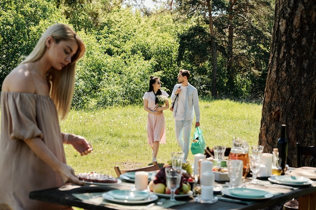 Blond girl putting assiette avec tarte maison sur la table servi pour le dîner avec des amis tandis que jeune couple parlant descendant pelouse verte