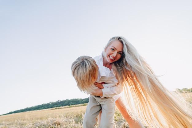 Blond petit garçon jouant avec maman aux cheveux blancs avec du foin dans le champ. été, temps ensoleillé, agriculture. enfance heureuse.
