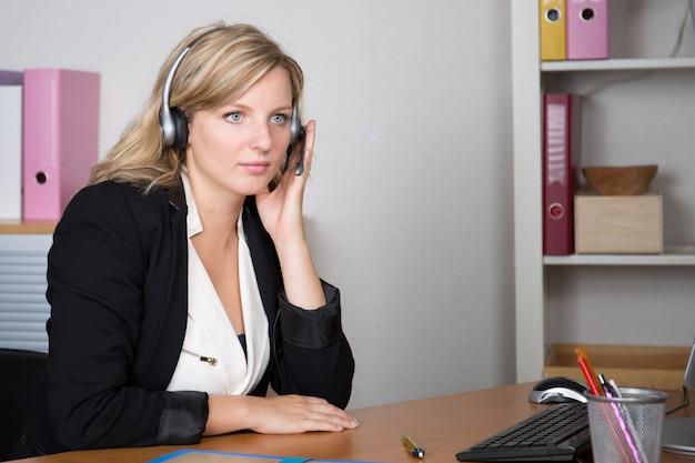 Blond sérieux beau jeune opérateur de téléphonie de soutien dans le casque