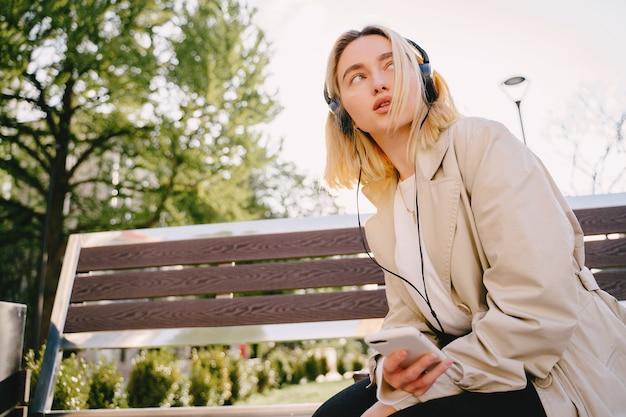Blonde assise sur un banc avec téléphone portable