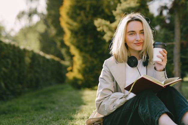 Blonde assise sur l'herbe avec un casque