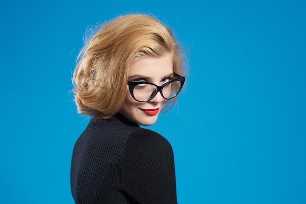 Blonde aux cheveux courts lèvres rouges lunettes veste noire fond isolé bleu