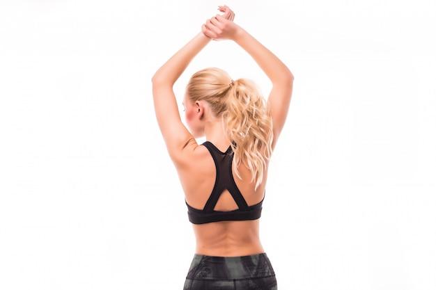 Blonde aux cheveux longs faire du sport pour son dos isolé sur blanc